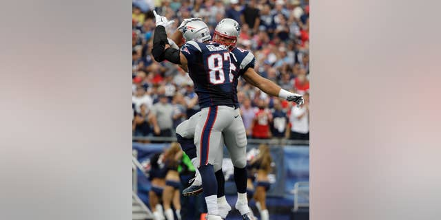 New England Patriots tight end Rob Gronkowski (87) celebrates his touchdown catch with fullback James Develin, rear, in the first half of an NFL football game against the Oakland Raiders, Sunday, Sept. 21, 2014, in Foxborough, Mass. (AP Photo/Steven Senne)