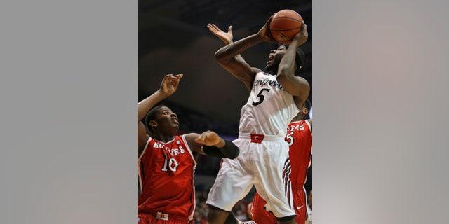 Cincinnati forward Justin Jackson (5) looks to shoot against Rutgers forward Junior Etou (10) during the first half of an NCAA college basketball game, Saturday, Jan. 11, 2014, in Cincinnati. (AP Photo/David Kohl)