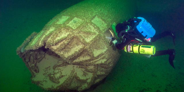 A diver looks at the nose of the B-29 bomber at the bottom of Lake Mead