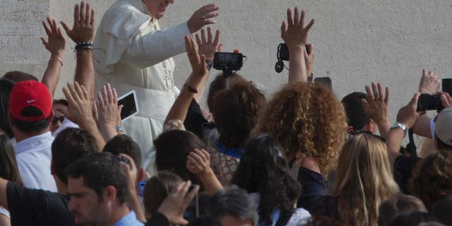 Pope Francis waves as he arrives for his weekly general audience in St. Peter's Square at the Vatican, Wednesday, Sept. 9, 2015. (AP Photo/Alessandra Tarantino)