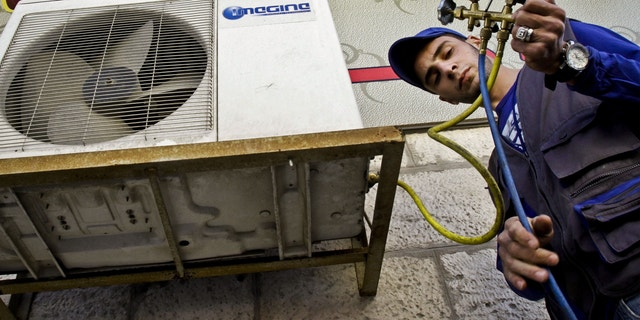 Mohammed Nabouti, a 21-year-old technician, fixes the air conditioner of a shop in Amman, Jordan on Monday, March 4, 2013. Just six months of learning to fix air conditioners changed Nabouti's life. Instead of drifting after high school like many of his jobless friends, Nabouti has taken a small loan to start his own business and recently got engaged. Nabouti's story points to a quick fix the unemployment-stricken Middle East might try until deeper economic reforms can kick in, experts say. This quick fix includes job training, micro loans and help in setting up businesses. (AP Photo/Raad Adayleh)