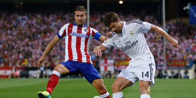 Real Madrid Xabi Alonso right, duels for the ball with Atletico Madrid's Gabi during a Spanish Super Cup soccer match at the Vicente Calderon stadium in Madrid, Spain, Friday, Aug. 22, 2014. (AP Photo/Daniel Ochoa de Olza)