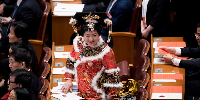 A delegate in ethnic minority costume walks to her seat after casting a vote during a plenary session of China's National People's Congress at the Great Hall of the People in Beijing, March 17, 2018.