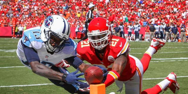 Tennessee Titans wide receiver Kendall Wright (13) scores a touchdown in front of Kansas City Chiefs cornerback Sean Smith (21) in the second half of an NFL football game in Kansas City, Mo., Sunday, Sept. 7, 2014. (AP Photo/Ed Zurga)