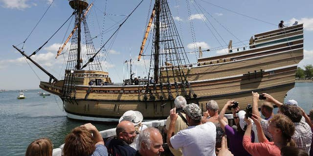 People on a wharf watch as the Mayflower II arrives in Plymouth Harbor on June 6, 2016. It is a  replica, built in 1957, of the famed ship that carried the Pilgrims to Massachusetts in 1620.