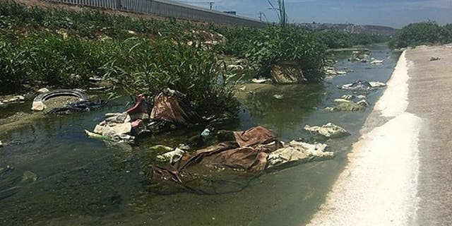 The Tijuana River, polluted with raw sewage, debris, and toxic waste and chemicals, flows into the ocean.