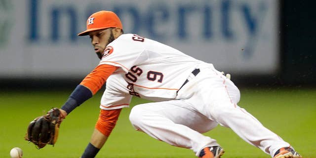 Houston Astros shortstop Marwin Gonzalez cannot catch up to a ball hit by Miami Marlins' Christian Yelich for a single during the sixth inning of a baseball game on Saturday, July 26, 2014, in Houston. (AP Photo/Patric Schneider)