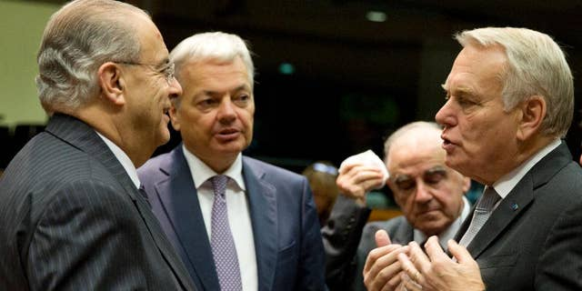 Cypriot Foreign Minister Ioannis Kasoulides, left, speaks with, from left, Belgian Foreign Minister Didier Reynders, Malta's Foreign Minister George Vella and French Foreign Minister Jean-Marc Ayrault during a round table meeting of EU foreign ministers at the EU Council building in Brussels on Monday, Dec. 12, 2016. EU foreign ministers hold talks Monday on the conflict in Syria, relations with Africa and migration. (AP Photo/Virginia Mayo)