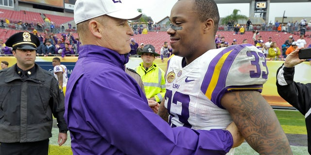 """FILE - In this jan. 1, 2014 file photo,LSU head coach Les Miles, left, congratulates MVP Jeremy Hill (33) after LSU defeated Iowa 21-14 in the Outback Bowl NCAA college football game in Tampa, Fla. LSU leading rusher Jeremy Hill says he's decided to enter the NFL draft. In an announcement made Monday, jan. 13, 2014,  on a social media website, Hill says he's grateful to LSU fans, friends, coaches and family and his decision was """"very difficult."""" (AP Photo/Chris O'Meara, File)"""