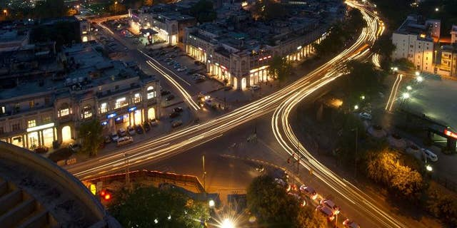 This photograph taken on April 18, 2013 shows the Indian capital's skyline as traffic drives around the outer circle of Connaught Place in the heart of New Delhi