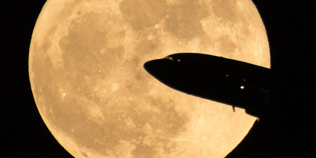 File photo - An airplane emanating from Ronald Reagan National Airport is seen to pass before the Moon while Sunday, December 3, 2017, Washington.