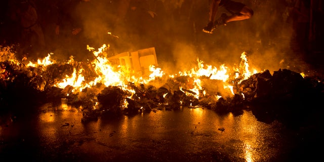 AP10ThingsToSee - A demonstrator jumps over a burning barricade at the Cinelandia Square during a march in support of teachers on strike in Rio de Janeiro on Monday, Oct. 7, 2013. Teachers have been on strike demanding better pay for nearly two months. (AP Photo/Felipe Dana, File)