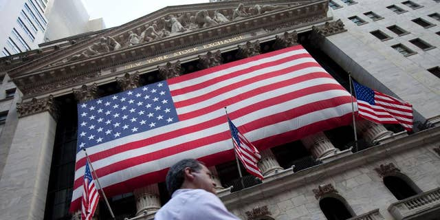 FILE - In this Monday, Aug. 8, 2011, file photo, a pedestrian walks past the New York Stock Exchange in New York. U.S. stocks headed higher in early trading, Friday, May 1, 2015, as the market bounces back from a steep decline the day before. Most Asian and European markets are closed for May 1, known as Labour Day in most of the world. (AP Photo/Jin Lee, File)