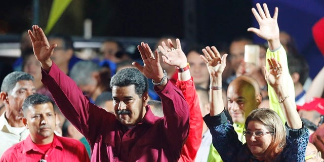 Venezuela's President Nicolas Maduro and his wife Cilia Flores wave to supporters at the presidential palace in Caracas, Venezuela, Sunday, May 20, 2018