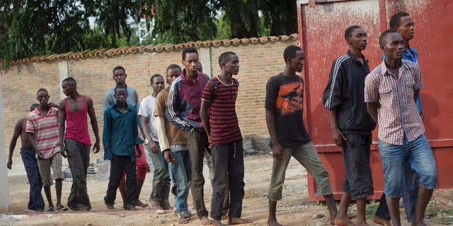 Men captured by the security forces, who were said by them to have been involved in Friday's attacks on military targets but which could not be independently verified, are paraded during a press conference at the country's intelligence service headquarters in the capital Bujumbura, Burundi, Saturday, Dec. 12, 2015. Violence from coordinated attacks on three army installations killed 87 people, an army spokesman said Saturday, while in the Nyakabiga neighborhood residents said they woke up to the shocking scene of dead bodies sprawled out on the streets, some of whom had their hands tied behind their backs. (AP Photo/Melanie Gouby)