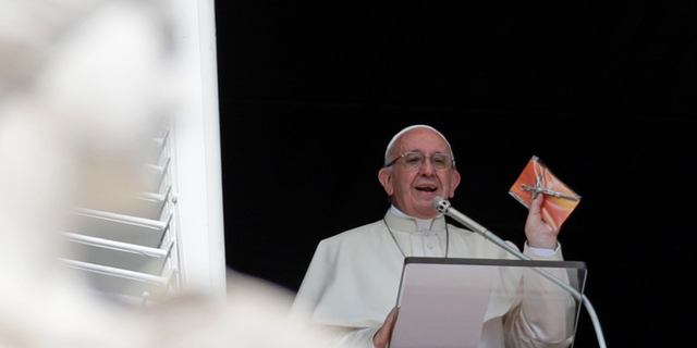 Pope Francis shows a crucifix during the Angelus noon prayer he delivers from the window of his studio overlooking St. Peter's Square at the Vatican, Sunday, Sept. 16, 2018. Tens of thousands of faithful have been treated to gifts from the pontiff, tiny crucifixes, distributed by nuns, refugees and some of Rome's homeless and poor after the pope's traditional Sunday appearance to pilgrims and tourists in the square. (AP Photo/Alessandra Tarantino)