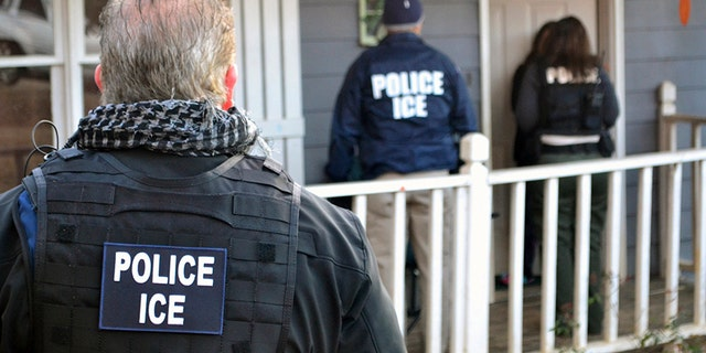 In this Feb. 9, 2017, file photo provided by U.S. Immigration and Customs Enforcement, ICE agents stand outside a home in Atlanta during a targeted enforcement operation aimed at immigration fugitives, re-entrants and at-large criminals living in the country illegally.