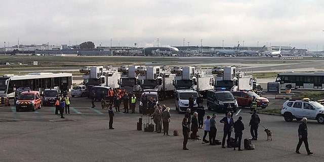 People are evacuated from a British Airways plane, on the tarmac of Charles de Gaulle airport, in Paris, Sunday, Sept. 17, 2017.