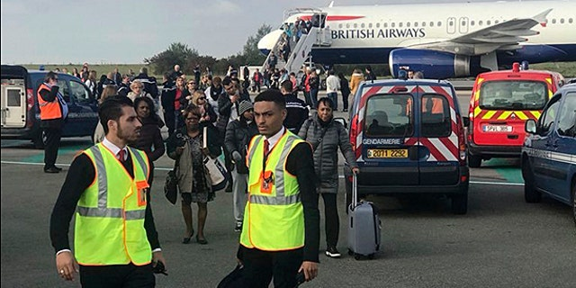 People are evacuated from a British Airways plane on the tarmac of Charles de Gaulle airport, in Paris, Sunday, Sept. 17, 2017.
