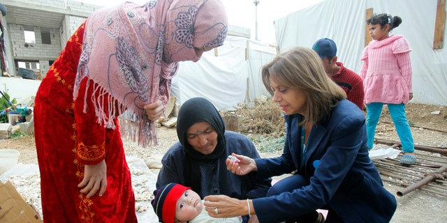 A UNICEF representative in Lebanon administers a polio vaccine to a baby at a Syrian refugee camp near Zahle town in the Bekaa Valley November 8, 2013. (REUTERS/Sharif Karim)