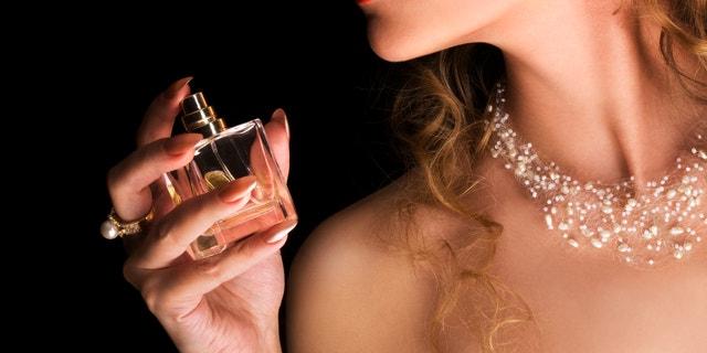 Beauty applying perfume on her neck
