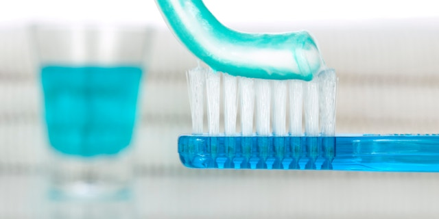 A blue toothbrush with toothpaste. Mouthwash and towels on the background