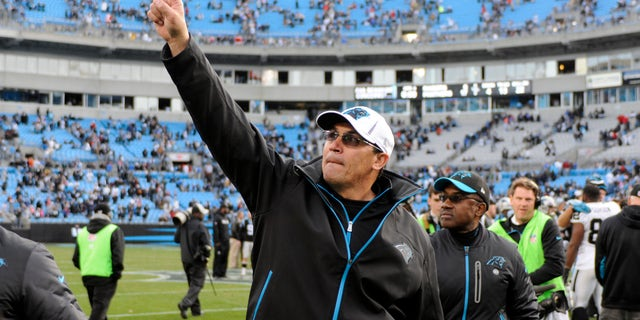Carolina Panthers coach Ron Rivera acknowledges fans as he walks off the field after the Panthers defeated the Oakland Raiders 17-6 in an NFL football game in Charlotte, N.C., Sunday, Dec. 23, 2012. (AP Photo/Mike McCarn)