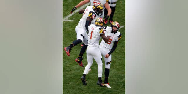 Maryland place kicker Brad Craddock, right, celebrates with Stefon Diggs (1) and Yannick Ngakoue (7) after kicking a 43-yard, game-winning field goal with 51 seconds left in the second half of an NCAA college football game against Penn State in State College, Pa., Saturday, Nov. 1, 2014. Maryland won 20-19. (AP Photo/Gene J. Puskar)