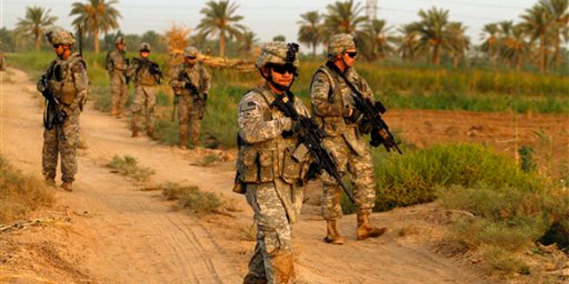 Army soldiers from 1st Battalion, 18th Infantry Regiment walk on a dirt road during an operation in Istaqlal, north of Baghdad, Iraq, Aug. 8.