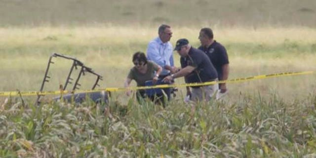 The partial frame of a hot air balloon is visible above a crop field as investigators comb the wreckage of Saturday's crash. (Ralph Barrera/Austin American-Statesman via AP)