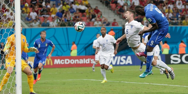 June 14, 2014: Italy's Mario Balotelli (9) heads the ball past England's Gary Cahill (5) and goalkeeper Joe Hart, left, to score Italy's second goal during the group D World Cup soccer match between England and Italy at the Arena da Amazonia in Manaus, Brazil.