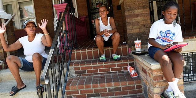 """Neighborhood residents Mary Johnson (C), her niece Erika Johnson (L) and her granddaughter Ayanna Herbert, 9, spend time near 2100 Homewood Avenue before the """"Huddle Up on the Wood"""" event and Cease Fire Community Jubilee during the 72-hour community-led Baltimore Ceasefire against gun violence in Baltimore, Maryland, U.S. August 4, 2017. REUTERS/Sait Serkan Gurbuz - RTS1AFF8"""