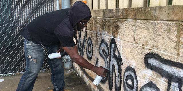 """In this Wednesday, Aug. 2, 2017, photo Tyree Colion spray paints the words """"No Shoot Zone"""" on a brick wall behind a convenience store, in a spot near where a 13-year-old girl was fatally shot in Baltimore County, Md. County police later arrested Colion for what they say was destruction of property, although he claimed he was given permission to paint the wall by a store clerk. (AP Photo/Juliet Linderman)"""