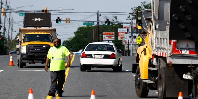 An emergency vehicle passes a roadblock near a scene where a Baltimore County police officer died, while investigating a suspicious vehicle, Monday, May 21, 2018, in Perry Hall, Md.