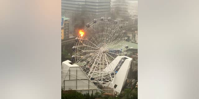 An empty passenger car of a Ferris wheel burns at Dinosaur Planet in Bangkok, Thailand on April 30, 2016.