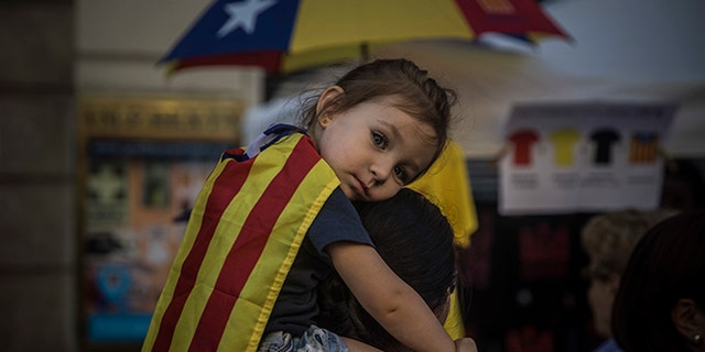 "A woman carries a girl on her shoulders wearing an ""estelada"" or independence flag, during the Catalan National Day in Barcelona."