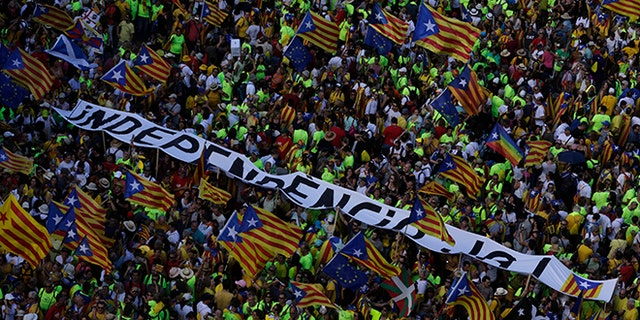"""Catalans with independence flags and a banner reading """"Independence now"""" gather during the Catalan National Day in Barcelona."""