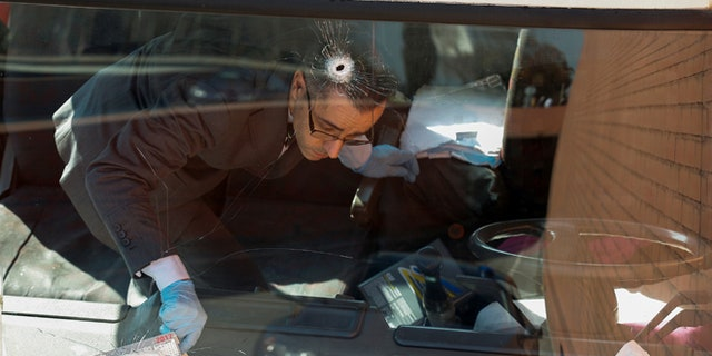 An investigator inside the truck with bullet holes in the windshield.