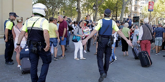 Police officers tell members of the public to leave the scene on a street in Barcelona, Spain, Thursday, Aug. 17, 2017.