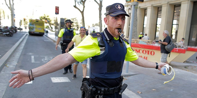 A police officer cordon off a street in Barcelona, Spain, Thursday, Aug. 17, 2017. Police in the northern Spanish city of Barcelona say a white van has jumped the sidewalk in the city's historic Las Ramblas district, injuring several people. (AP Photo/Manu Fernandez)