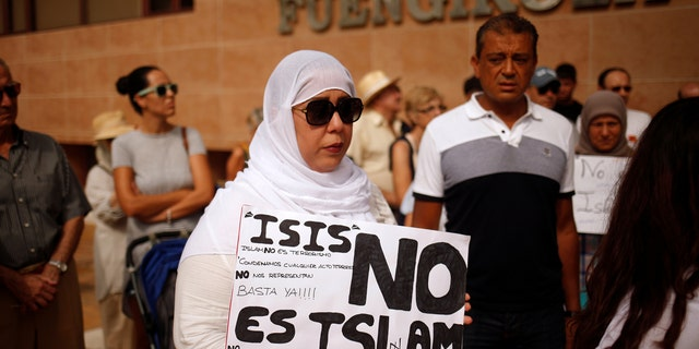"""A Muslim woman holds a sign that reads """"ISIS is not Islam"""" as she takes part in a gathering of different religious groups in rejection of the attack in Barcelona."""