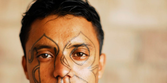 An imprisoned member of street gang Barrio 18 poses for a photograph at the Izalco prison, about 65 km (40 miles) from San Salvador.