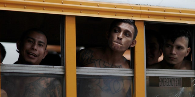 Members of the Barrio 18 Gang wait on a bus as 1282 inmates are transferred from the cojutepeque jail in Cojutepeque, El Salvador