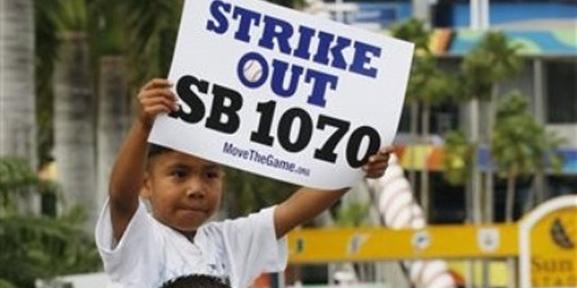 Elias Perez, 5, sits on the shoulders of Gerardo Reyes of Immokalee, Fla. , as they protest the Arizona Immigration Law SB 1070 outside Sun Life Stadium, before a baseball game between the Florida Marlins and the Arizona Diamondbacks, Monday, May 17, 2010 in Miami. (AP)