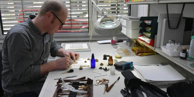 An expert works on the ancient papyrus.