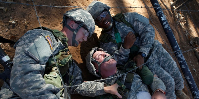 Pvts. Sean Christopher Welliver, left, and John Hubbard, right, drag fellow Pvt. William Weaver (C) through an obstacle course as part of a first aid training exercise.