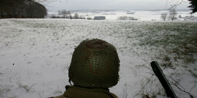 A man dressed as a U.S. soldier looks at the site of the Battle of the Bulge before a ceremony at the Mardasson World War II memorial monument in Bastogne, December 18, 2004. Belgium and Luxembourg commemorate the Battle of the Bulge, a last-ditch German offensive on December 16, 1944 which was the bloodiest land battle of WW2 involving US troops, who suffered some 80,000 casualties, of which 19,000 were killed. REUTERS/Francois Lenoir  FLR/SM - RTRILAS