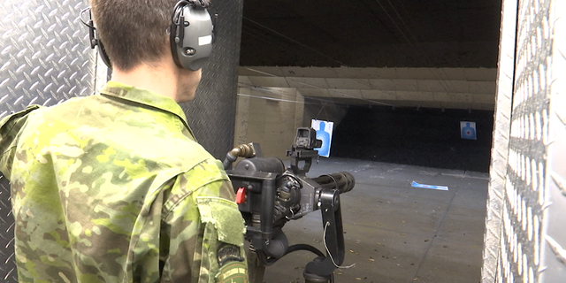 A staffer positions and readies the minigun, a machine gun with a high rate of fire, for use at the target range