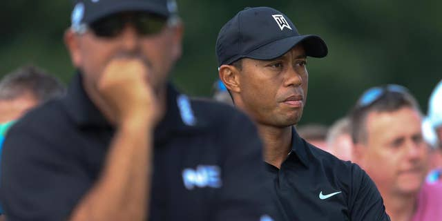Tiger Woods of the US, right, and Angel Cabrera of Argentina wait to play on the 10th tee box during the second day of the British Open Golf championship at the Royal Liverpool golf club, Hoylake, England, Friday July 18, 2014. (AP Photo/Peter Morrison)