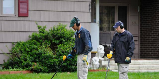 In this Thursday, May 10, 2012, file photo, law enforcement agents search the yard at the home of reputed Connecticut mobster Robert Gentile in Manchester, Conn.